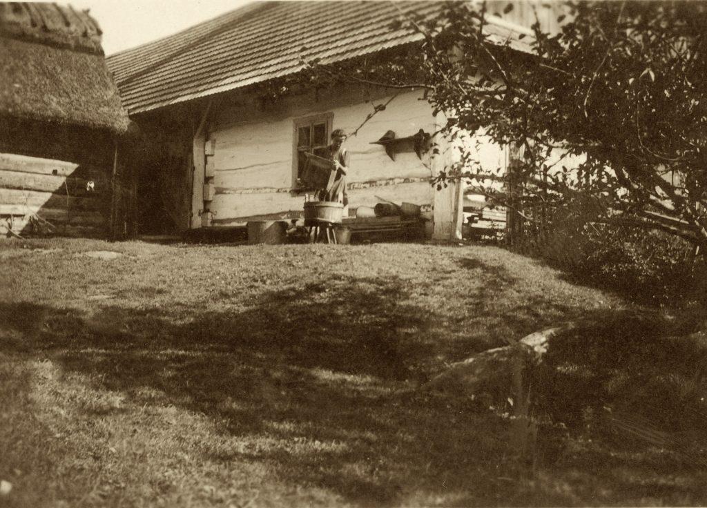 Archiwalne zdjęcie Chałupy Szylarów. Na pierwszym planie kobieta oporządzająca ule. W tle dom. Po lewej stronie szopa.