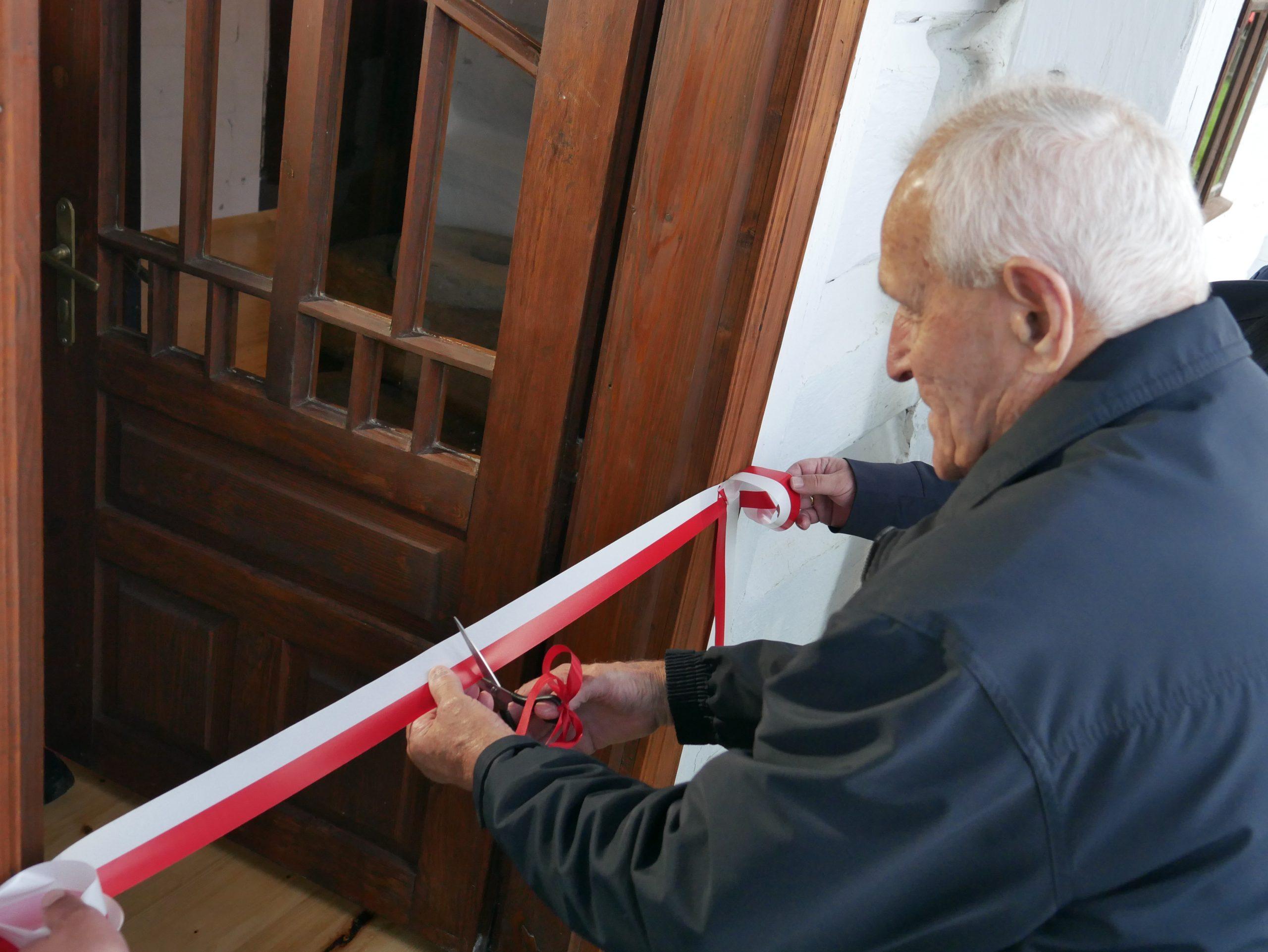 Pan Eugeniusz Szylar przeciwna wstęgę, otwierając w ten sposób Chałupę Szylarów.